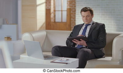 Handsome man business suit working on tablet, smiling at camera