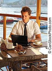 Handsome man businessman work at the laptop in restaurant
