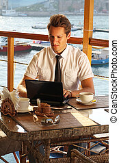 Handsome man businessman work at the laptop in restaurant