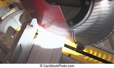 handsome man carpenter using a circular saw while installing...