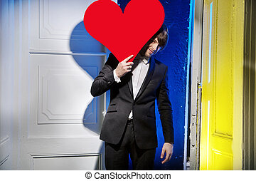 Handsome man carrying a large heart