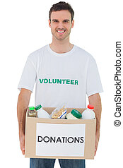 Handsome man carrying donation box with food
