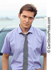 Handsome Man casually leaning against the car, outdoor portrait