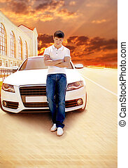 Handsome man casually leaning against the white car at sunset,