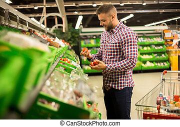 Handsome Man Choosing Fresh Tomatoes in Supermarket