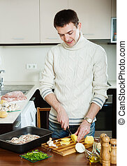 Handsome man cooking meat with mushrooms and potatoes