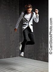 Handsome man dancing on the wooden floor