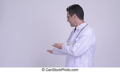 Handsome man doctor showing something against white...