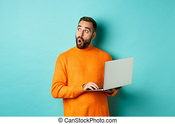 Handsome man doing online shopping, looking up thoughtful while using laptop, standing over light blue background