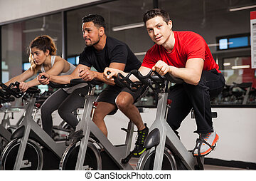 Handsome man doing spinning at a gym - Portrait of a good...