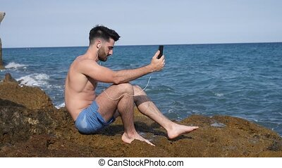 Handsome man doing videochat at sea - Young shirtless...