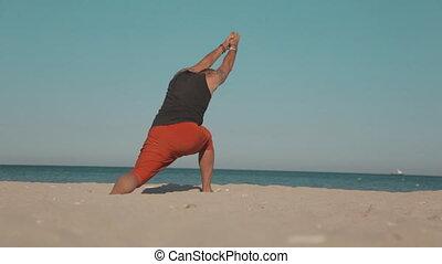 Handsome man doing yoga in front of ocean