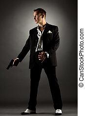 Handsome man dressed as gangster holding gun