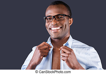 Handsome man dressing up. Handsome young black man dressing up his shirt and smiling at camera while standing against grey background