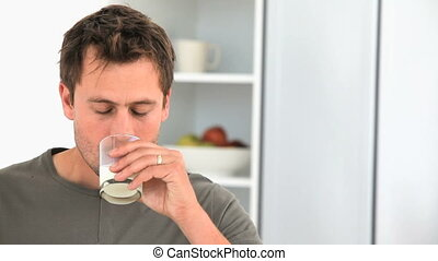 Handsome man drinking a glass of milk
