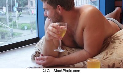 man drinking beer from a glass and eat fish, lying on the floor