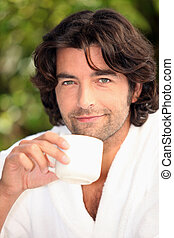 handsome man drinking his coffee in the garden