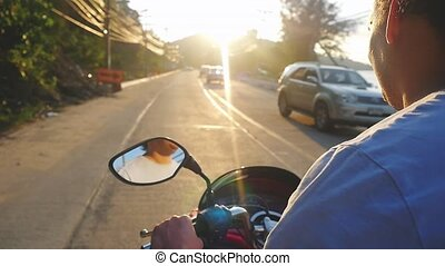 Handsome man driving motorbike on tropical island during...