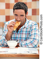 Handsome man eating a croissant