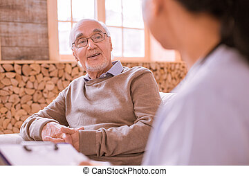 Handsome man enjoying pleasant communication with practitioner