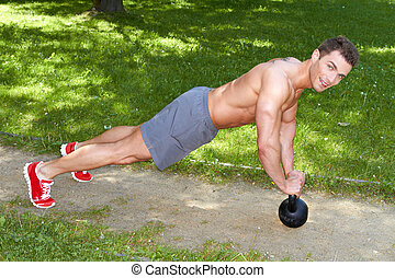 Handsome man exercises with kettlebell in park