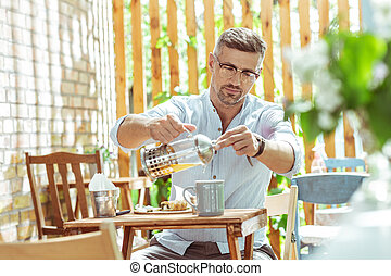 Handsome man filling his cup with tea.
