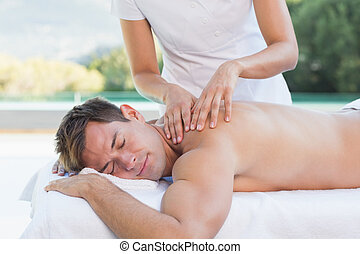 Handsome man getting a massage poolside