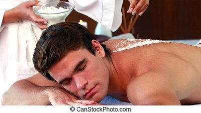 Handsome man getting a salt scrub t