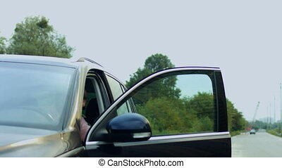Handsome man getting out of parked car on roadside -...