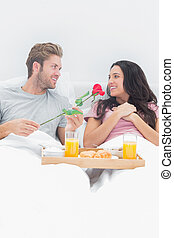 Handsome man giving a rose to his wife during breakfast in...