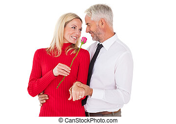 Handsome man giving his wife a pink rose