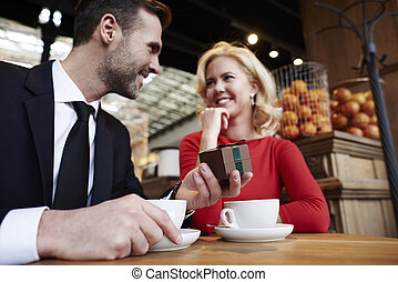 Handsome man giving woman gift over coffee meeting
