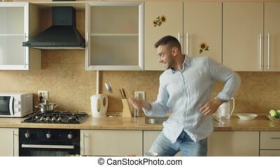 Handsome man having fun in the kitchen fencing with ladle and spoon while cooking breakfast at home