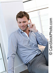 Handsome man having phone call at work