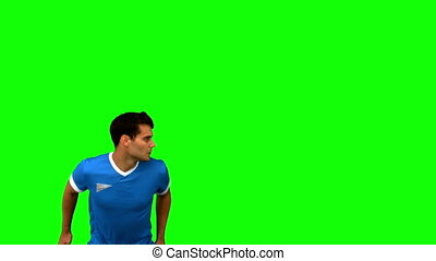 Handsome man heading a football on green screen in slow...
