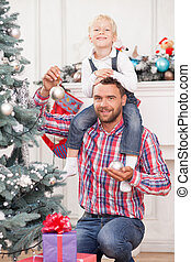 Handsome man helps child to decorate New Year tree