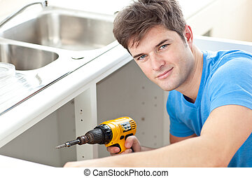 Handsome man holding a drill repairing a kitchen sink at home