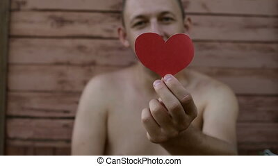 Handsome man holding a paper heart