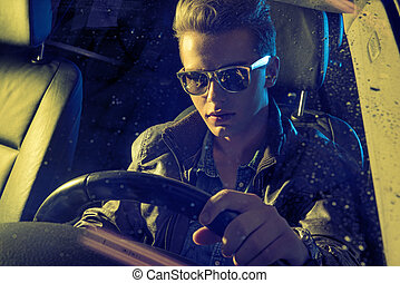 Handsome man holding a steering wheel