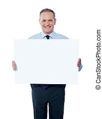 Handsome man holding blank white billboard