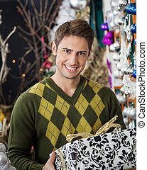Handsome Man Holding Christmas Gift In Store