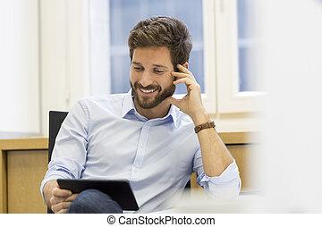 Handsome man holding digital tablet in office