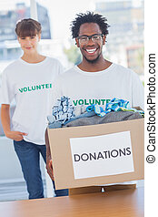 Handsome man holding donation box next to a colleague -...