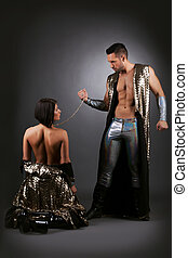 Handsome man holding his sexy slave in chains