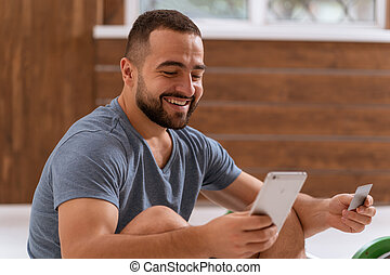 Handsome man holding smartphone doing sport bets and gambling online or buying online equipment with a debit or credit card. Sports betting apps on smartphone. Modern digital sports life