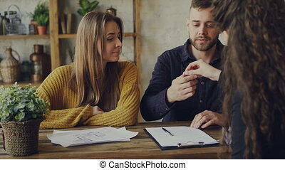 Handsome man house buyer is signing sales agreement with housing agent, getting key and hugging his girlfriend after making deal with realtor. Buying real estate concept.
