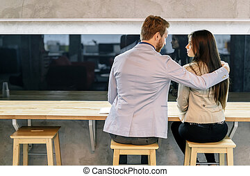 Handsome man hugging a woman in a bar