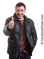 Handsome man in a down jacket showing his thumb up
