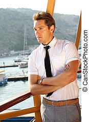 handsome man in a white shirt looking away, sunshine outdoors, sea port