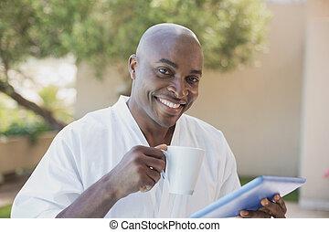 Handsome man in bathrobe using tablet at breakfast outside ...